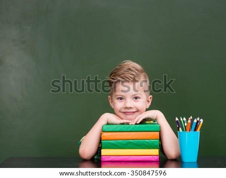 Portrait of a happy schoolboy in classroom - stock photo