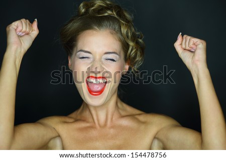 Portrait of a happy screaming woman with hands raised on a dark background