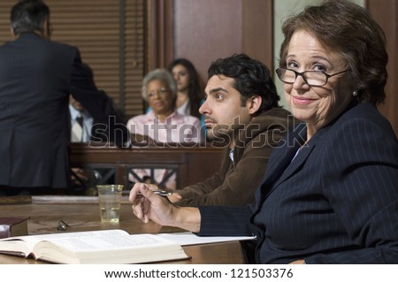 Portrait of a happy senior advocate sitting with client during prosecution in court house - stock photo