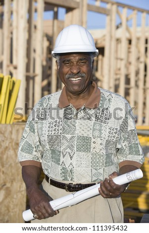 Portrait of a happy senior African American male architect holding blueprint at construction site - stock photo
