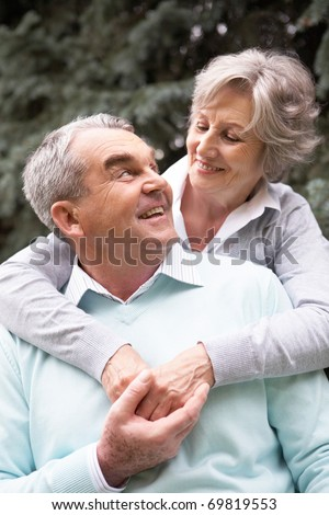Portrait of a happy senior couple embracing and looking at each other - stock photo