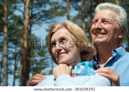 Portrait of a happy senior couple in autumn  forest - stock photo