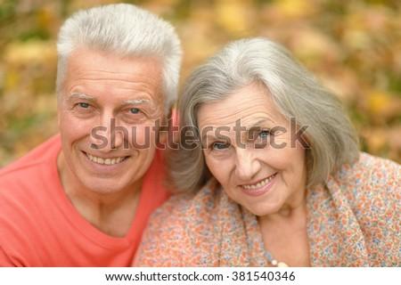 Portrait of a happy senior couple in autumn park - stock photo