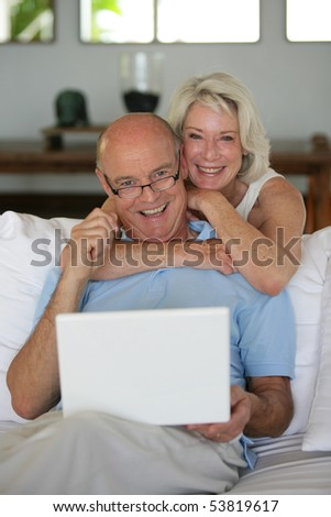 Portrait of a happy senior couple in front of a laptop computer - stock photo