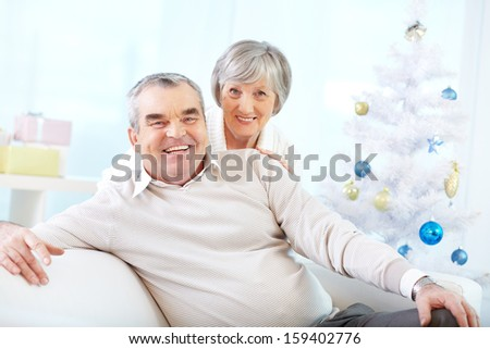Portrait of a happy senior couple looking at camera on background of decorated Christmas tree  - stock photo
