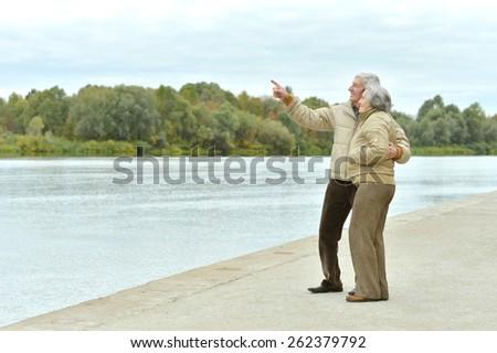 Portrait of a happy senior couple near lake - stock photo
