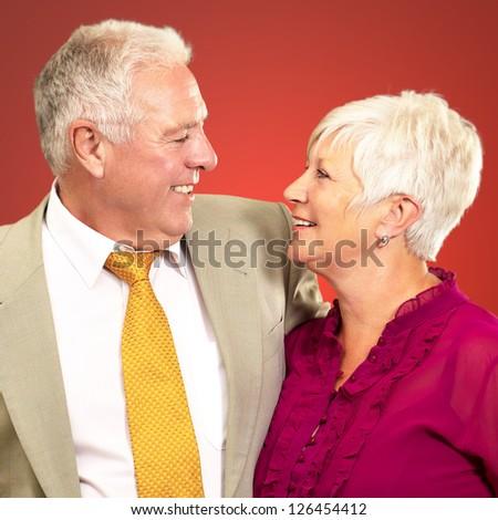Portrait Of A Happy Senior Couple On Orange Background - stock photo