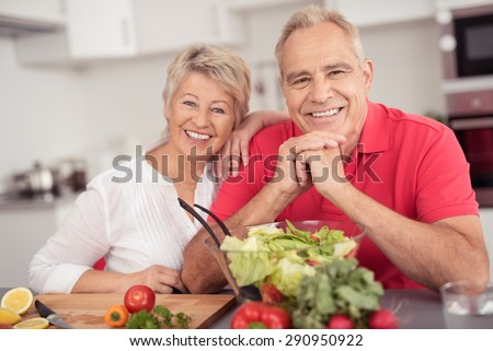 Portrait of a Happy Senior Couple Sitting at the Kitchen Table with a Bowl of Fresh Salad, Smiling at the Camera. - stock photo