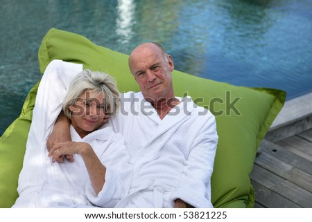 Portrait of a happy senior couple with bathrobes - stock photo