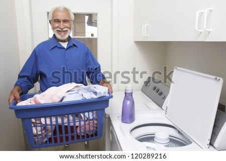 Portrait of a happy senior man with laundry basket in the bathroom