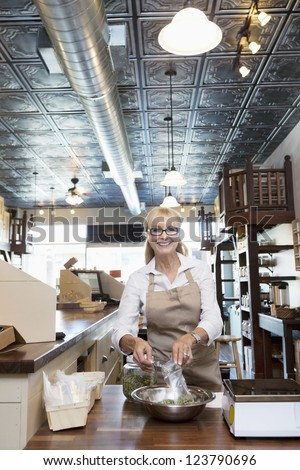 Portrait of a happy senior merchant pouring spice from jar in store - stock photo
