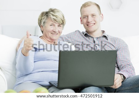 Portrait of a happy senior woman and her grandson using a laptop