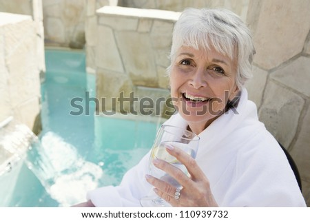 Portrait of a happy senior woman enjoying her drink by pool - stock photo