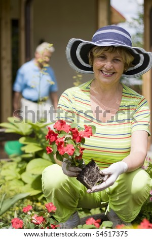 Portrait of a happy senior woman gardening with her husband in background