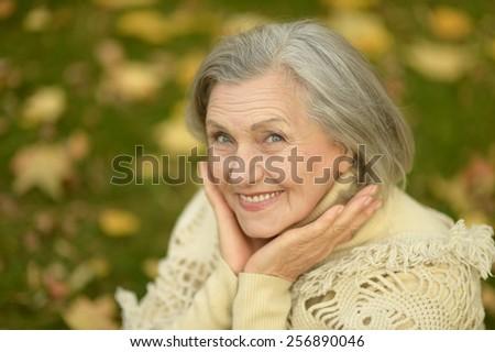 Portrait of a happy senior woman in autumn park - stock photo
