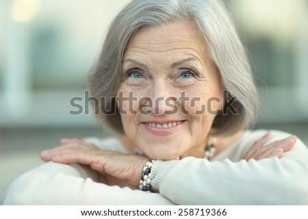 Portrait of a happy Senior woman in autumn park - stock photo