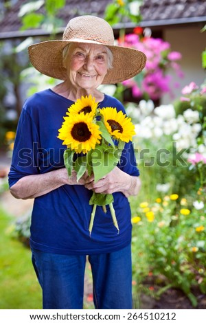 Portrait of a Happy Senior Woman in Blue Clothing with Garden Hat Holding Pretty Sunflowers. - stock photo