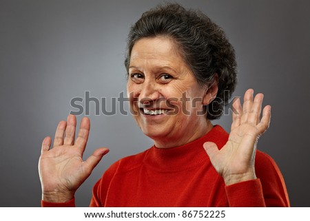 Portrait of a happy senior woman on gray background - stock photo