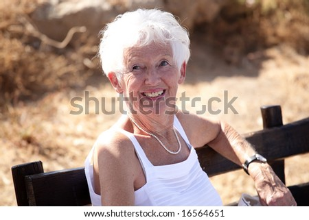 Portrait of a happy senior woman relaxing outdoors - stock photo