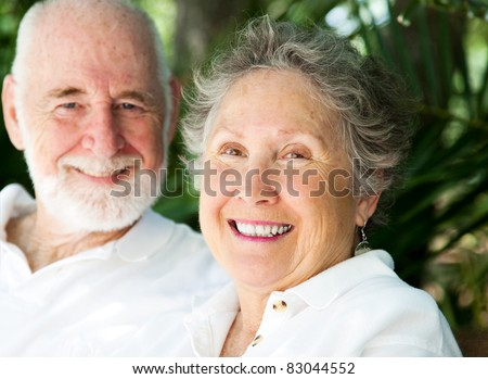 Portrait of a happy senior woman with her loving husband in background. - stock photo