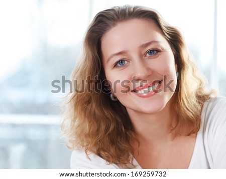 Portrait of a happy smiling blond woman near the window - stock photo