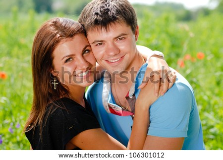Portrait of a Happy smiling couple: handsome young man hugging gently beautiful young woman outdoors on a bright sunny day of spring or summer on the green garden or park background