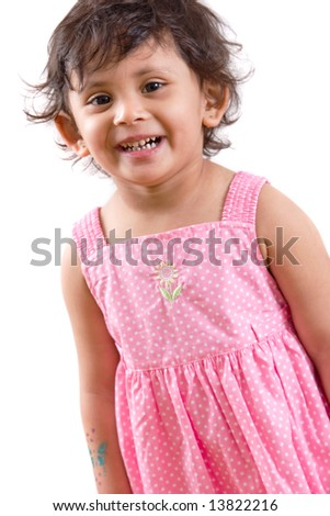 Portrait of a happy, smiling east Indian girl in a pink polka dot dress