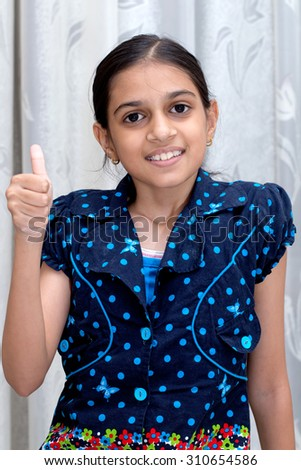 portrait of a happy smiling  indian young girl  dressed in blue top with polka dots showing thumbs up - stock photo