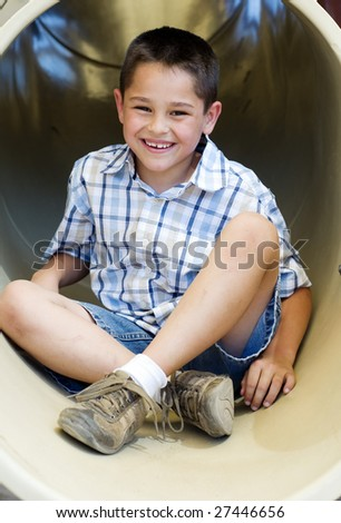Portrait of a happy smiling little boy playing outside in park - stock photo