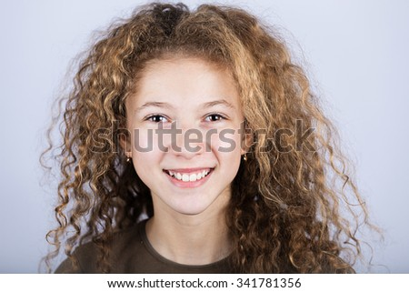 Portrait of a  Happy Smiling  little girl  with curly hair over white background.Happiness,Childhood. - stock photo