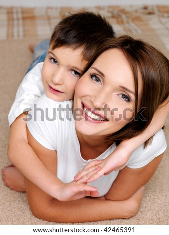 Portrait of a happy smiling  mother  with her little son lying on her back