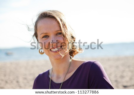 Portrait of a happy, smiling woman at the beach during summer.