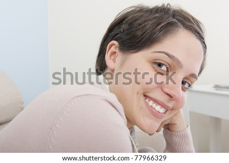 Portrait of a happy smiling young adult  latina woman looking to the camera - stock photo