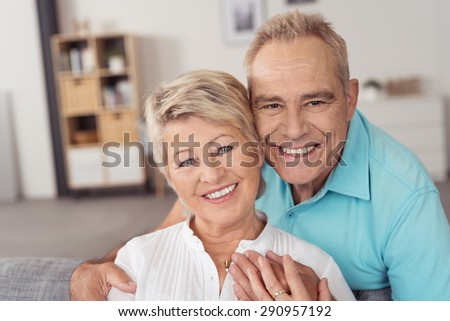 Portrait of a Happy Sweet Middle Aged Couple Smiling at the Camera While at the Living Area Inside the House. - stock photo