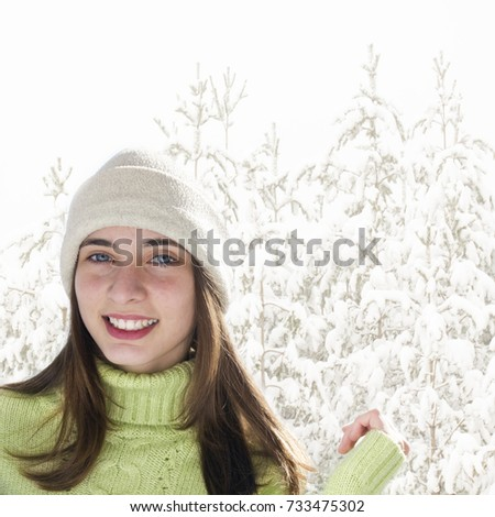 Portrait of a happy teenage girl in the snow