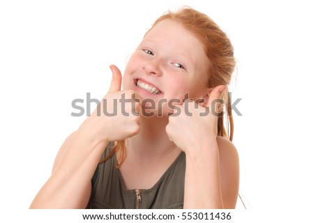 Portrait of a happy teenage girl showing thumbs up on white background