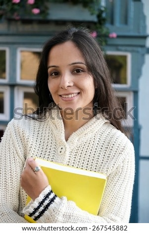 Portrait of a happy teenager standing with books. - stock photo
