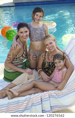 Portrait of a happy three generation family with arm around at poolside - stock photo