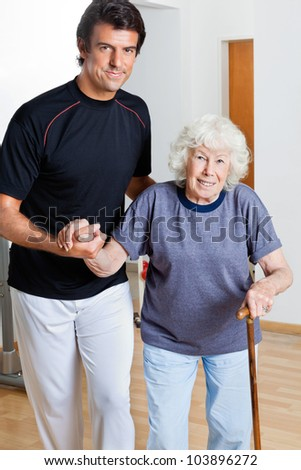 Portrait of a happy trainer assisting woman with walking stick - stock photo