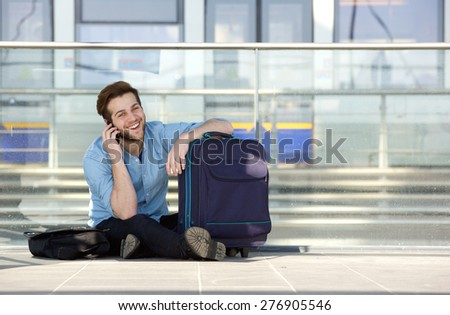 Portrait of a happy traveler waiting at station and talking on cell phone - stock photo