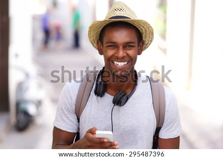 Portrait of a happy traveler walking in town with mobile phone