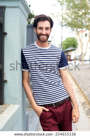 Portrait of a happy trendy man in striped shirt leaning against wall outdoors - stock photo
