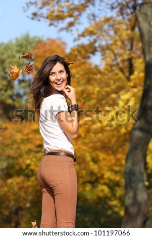 Portrait of a happy woman against yellow leaves - stock photo