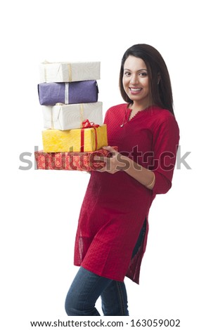 Portrait of a happy woman holding a stack of gifts - stock photo