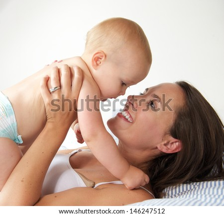 Portrait of a happy woman holding baby and smiling in bed - stock photo
