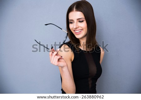 Portrait of a happy woman holding glasses and looking away. Wearing black sexy dress. Posing over gray background - stock photo