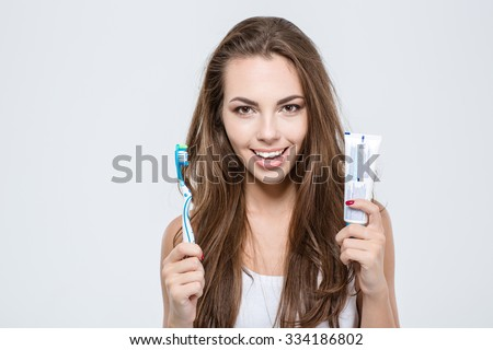 Portrait of a happy woman holding toothbrush and toothpaste isolated on a white background and looking at camera - stock photo