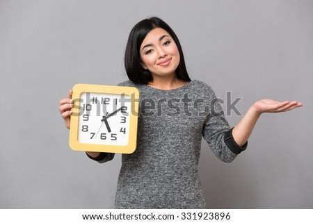 Portrait of a happy woman holding wall clock and copyspace on the palm over gray background - stock photo