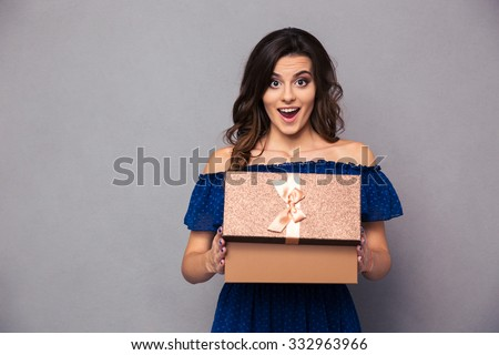 Portrait of a happy woman opening gift box and looking at camera over gray background - stock photo