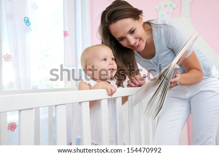 Portrait of a happy woman reading a book to a cute baby  - stock photo